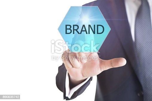 istock Businessman pressing 'BRAND' button on virtual touch screen on blue technology background. 890635742