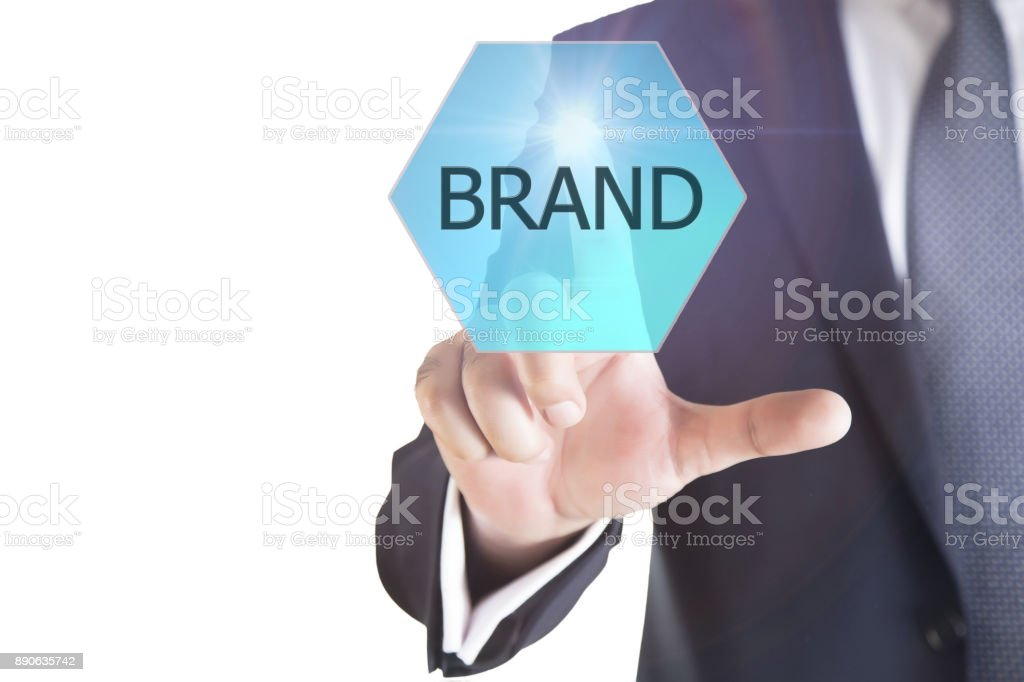 Businessman pressing 'BRAND' button on virtual touch screen on blue technology background. stock photo