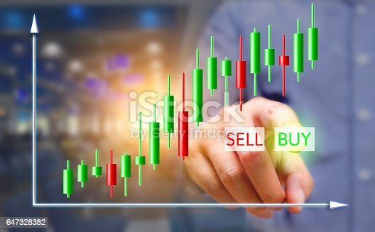 istock Businessman pressing buy button on virtual screens with stock chart. 647328382