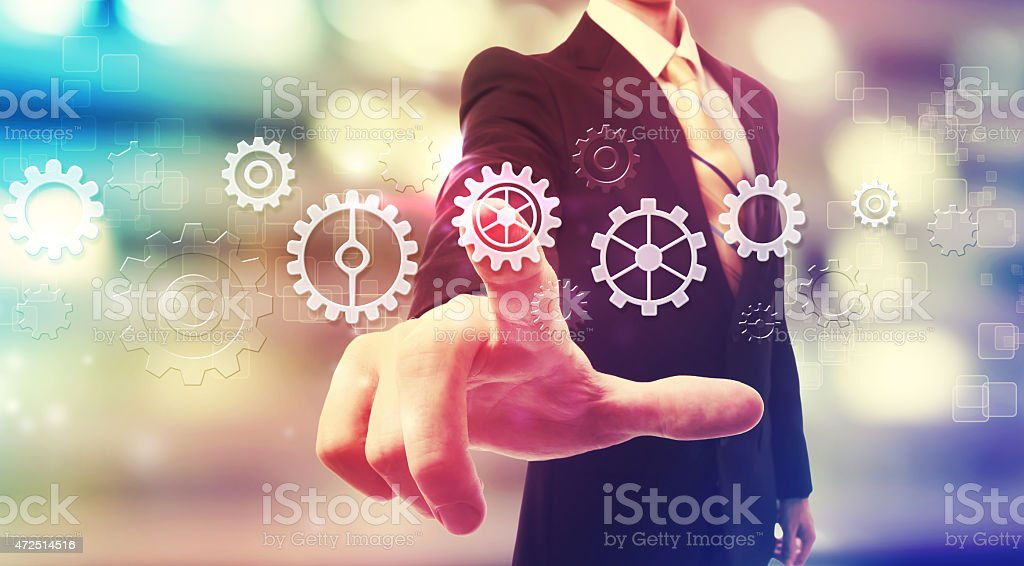 Businessman pressing gear icons stock photo