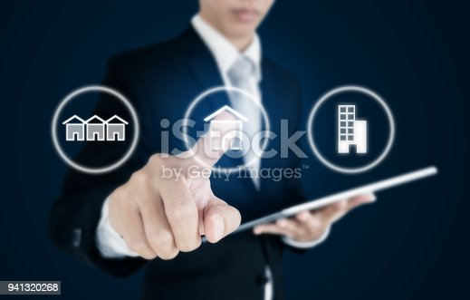 istock Businessman pressing real estate icons on screen. Business investment in real estate, town house, single home and condominium 941320268