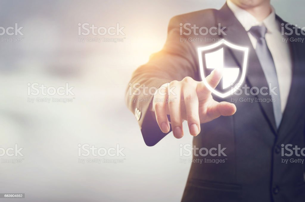 Businessman pressing shield security button on virtual screens stock photo