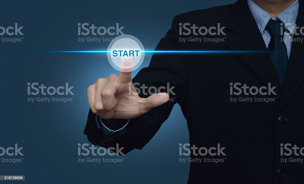 Businessman pressing start button with spot light on blue background stock photo