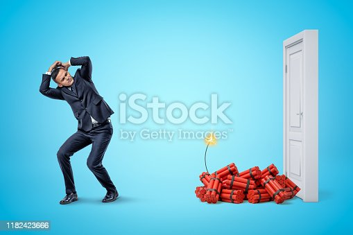Businessman protecting himself with hands and red dynamite sticks with lit fuse next to white doorway on blue background. Businessman and management. Financial risks. Explosive materials.
