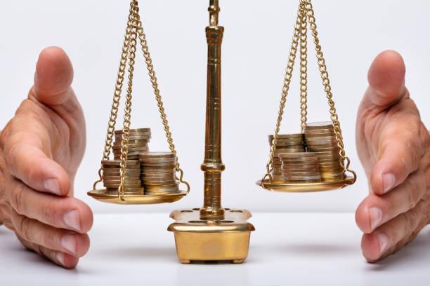 geschäftsmann schützt gerechtigkeitsskala mit münzen - wirtschaftsrecht stock-fotos und bilder