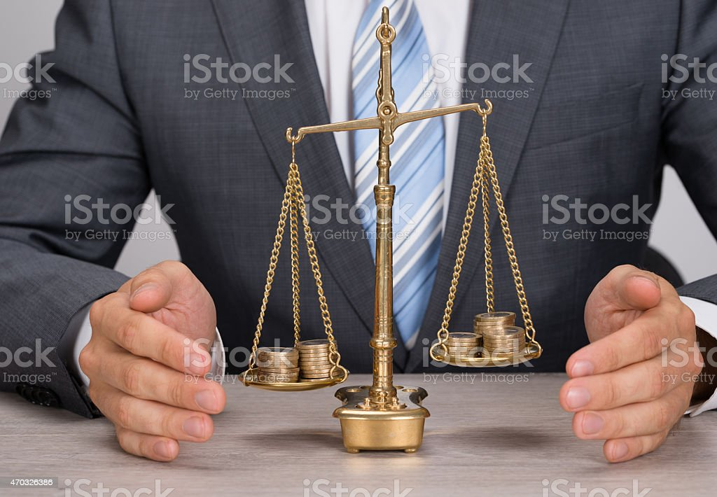 Businessman Protecting Justice Scale With Coins stock photo