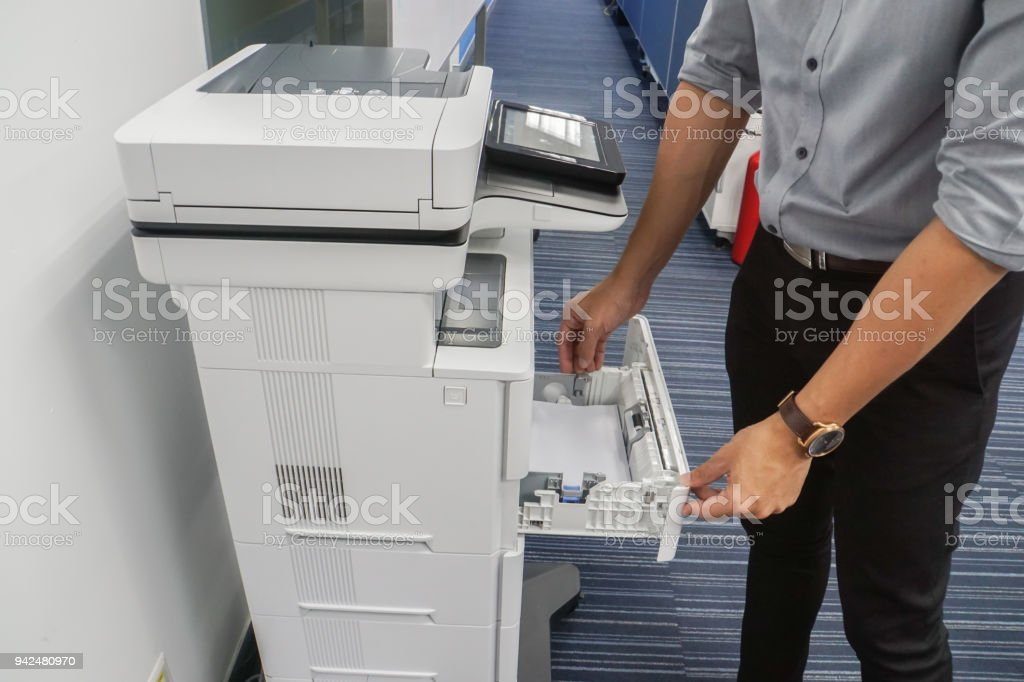 businessman pull multi function office printer tray to put paper for printing documents stock photo