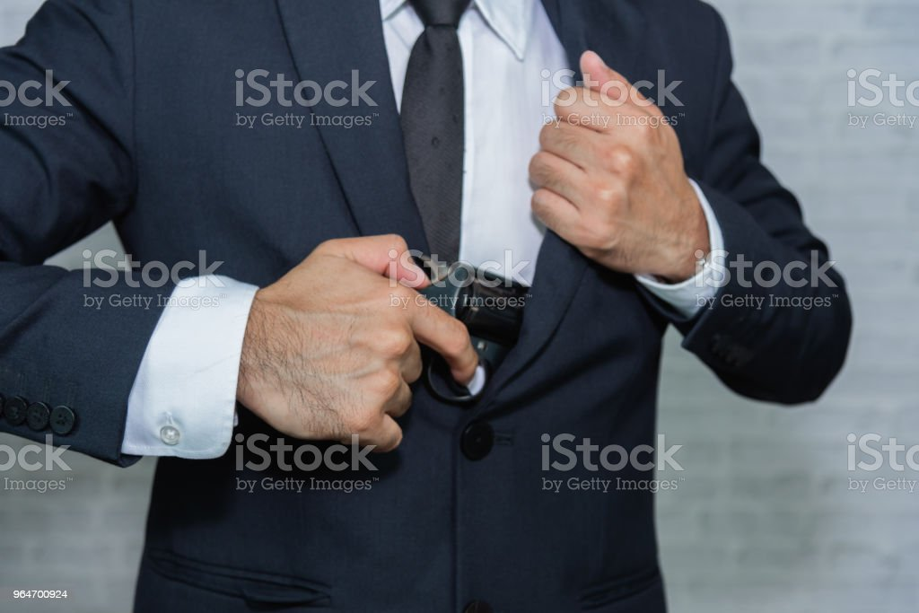 Businessman pull out gun from jacket royalty-free stock photo