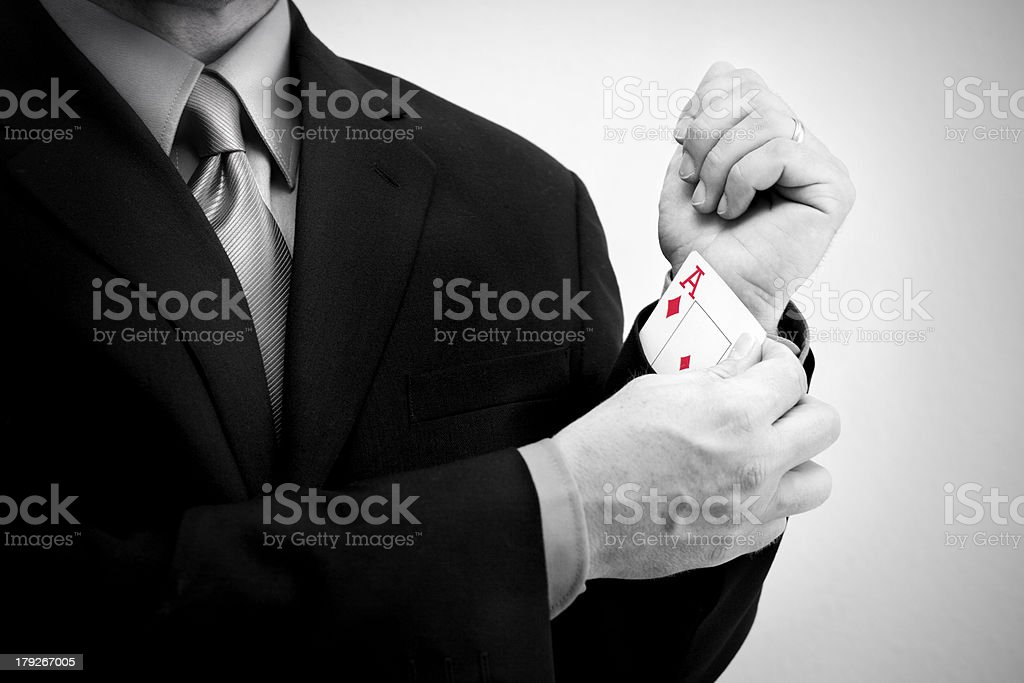 Businessman Pulling Ace from Sleeve stock photo