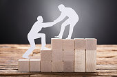 Businessman Pulling Colleague While Standing On Wooden Blocks