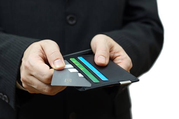 geschäftsmann ziehen kreditkarte von brieftasche zu zahlen - karte ziehen stock-fotos und bilder