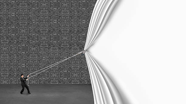 businessman pulling down white curtain covering old dark brick w stock photo