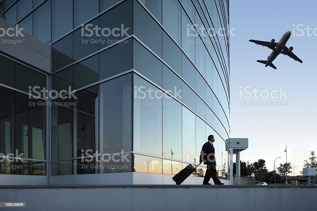 businessman pulling is luggage outdoors stock photo