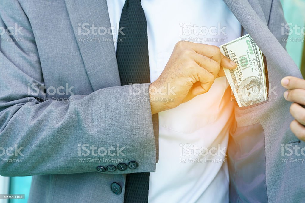 Businessman pulling money from his pocket suit stock photo