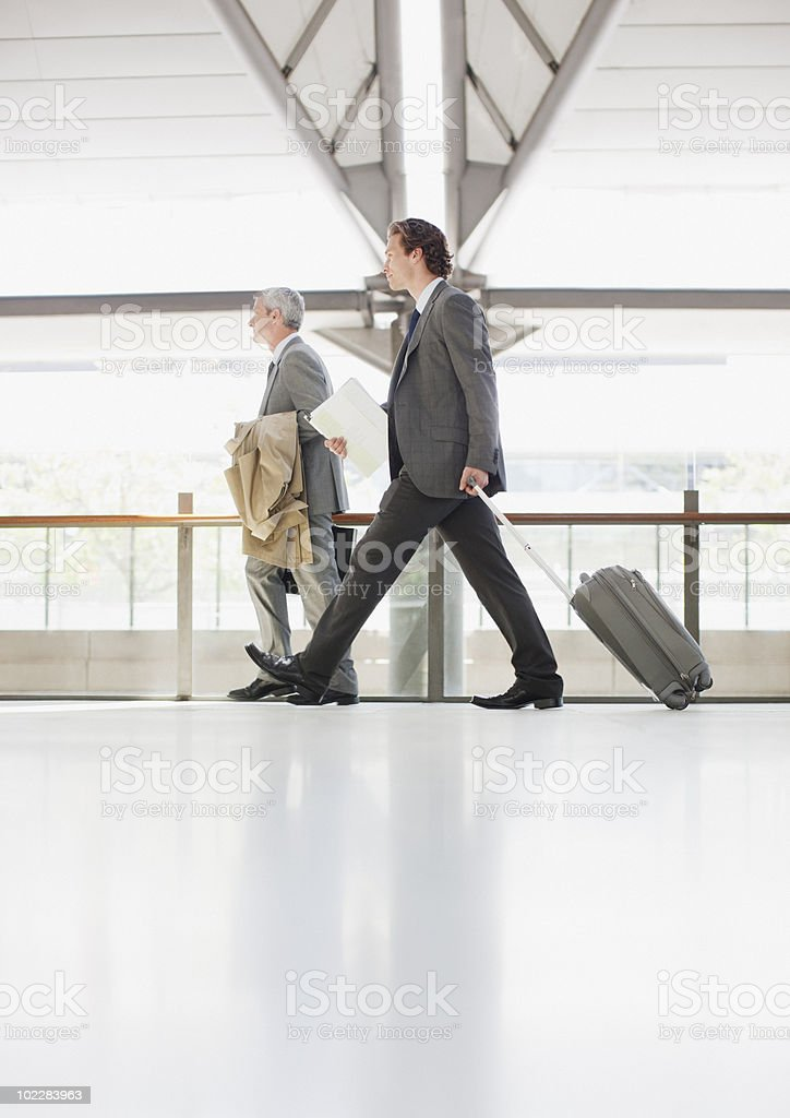 Businessman pulling suitcase in train station royalty-free stock photo