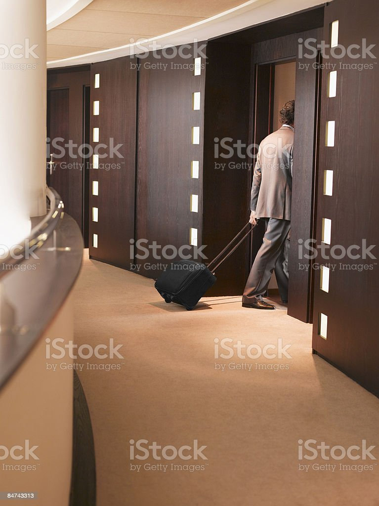 Businessman pulling suitcase into elevator royalty-free stock photo