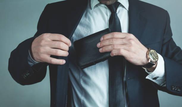 ビジネスマンはスーツのポケットに革財布をプルします。 - 財布 ストックフォトと画像