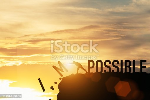 Businessman push impossible wording to possible wording on top of mountain with sunlight. Positive mindset concept.