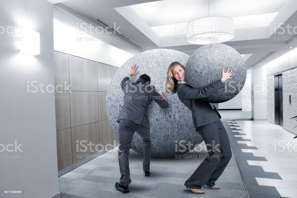 Businessman Pushes And Businesswoman Carries Large Stone In Office Setting stock photo