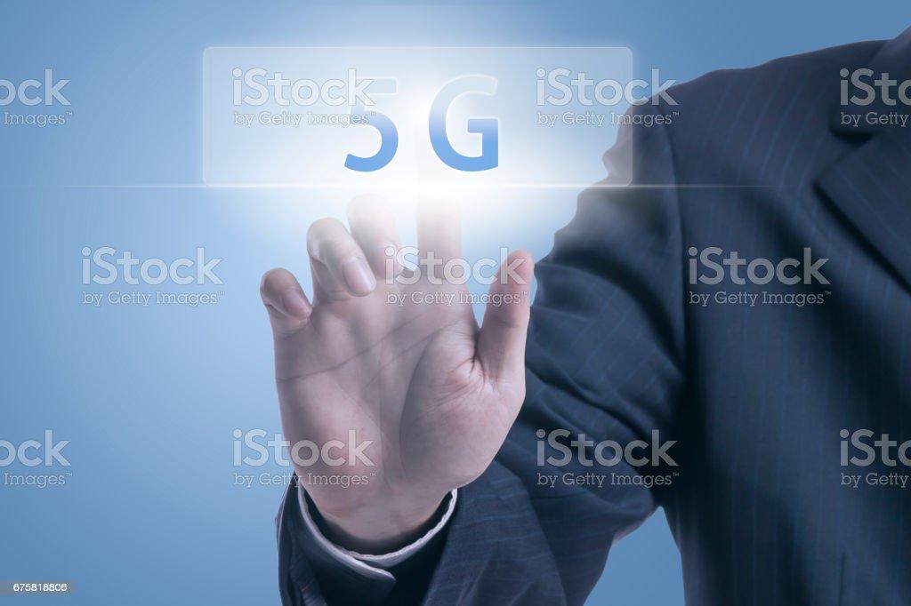 Businessman pushing 5G icon - Foto stock royalty-free di Abbigliamento formale