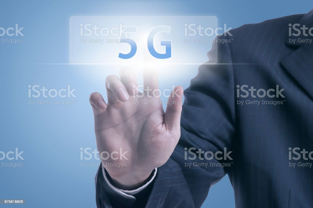 Businessman pushing 5G icon stock photo