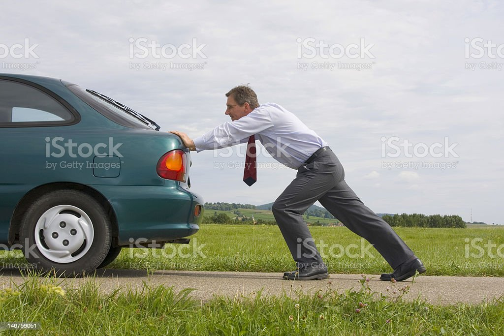 Businessman pushing a car stock photo