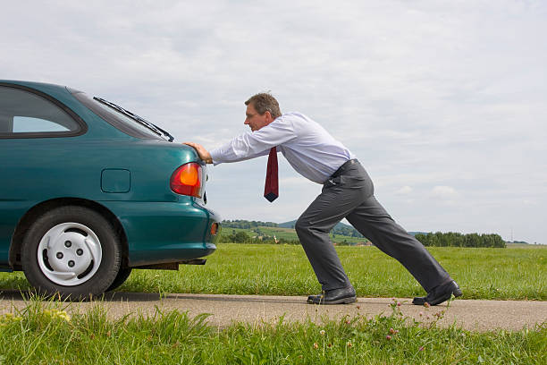 Businessman pushing a car​​​ foto