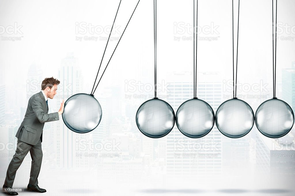 A businessman pushing a giant Newton ball stock photo