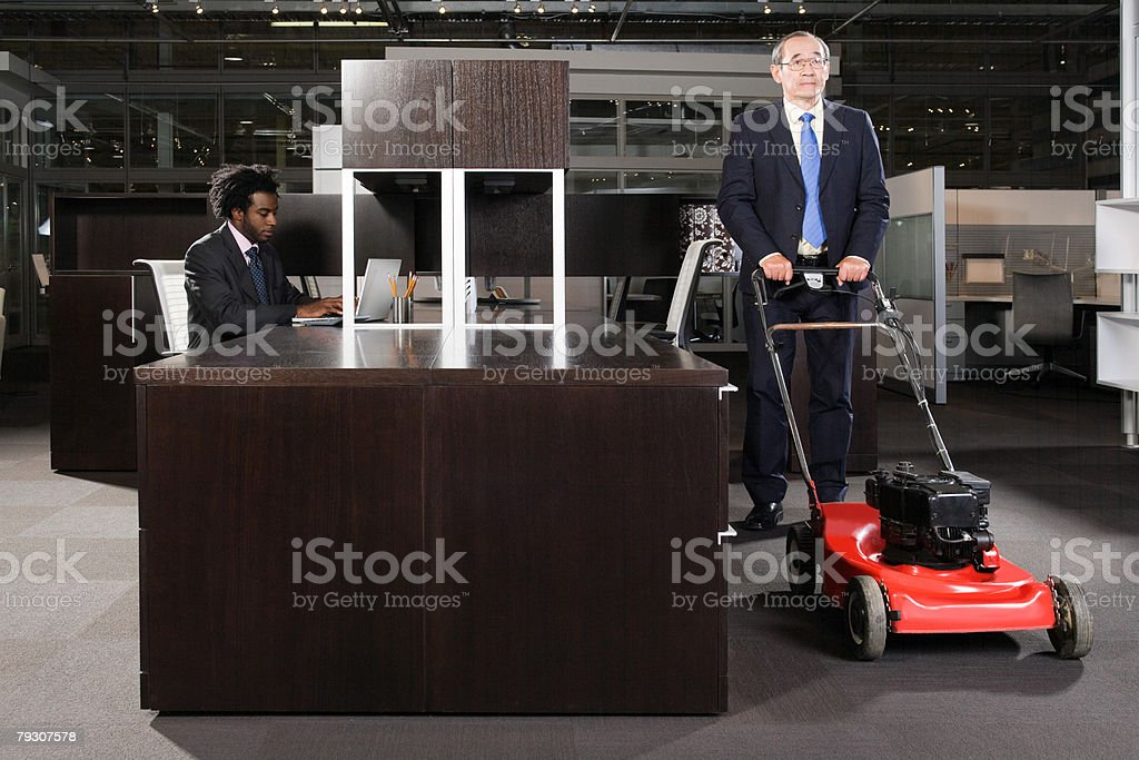 A businessman pushing a lawn mower in an office 免版稅 stock photo