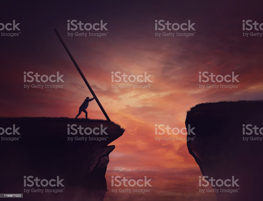 Businessman pushing a long beam, creating an improvised bridge to cross the abyss obstacle. Cover the gap and reach other side of the cliff. Mission accomplishment, overcome and success concept. - Royalty-free Achievement Stock Photo