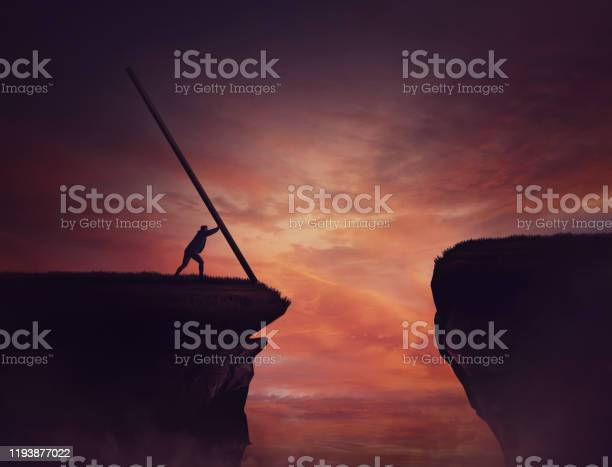 Photo of Businessman pushing a long beam, creating an improvised bridge to cross the abyss obstacle. Cover the gap and reach other side of the cliff. Mission accomplishment, overcome and success concept.