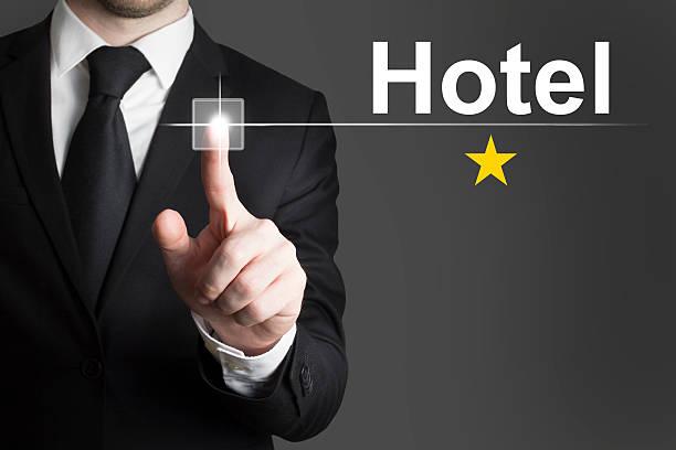 geschäftsmann schieben knopf einem sterne-hotel - flugticket vergleich stock-fotos und bilder