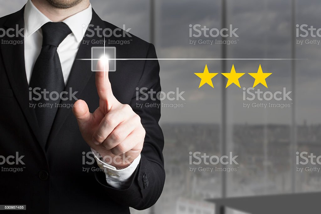 businessman pushing button three stars stock photo