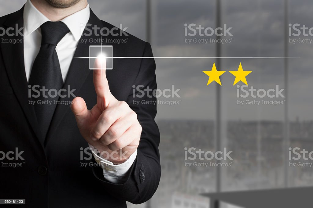 businessman pushing button two star rating stock photo