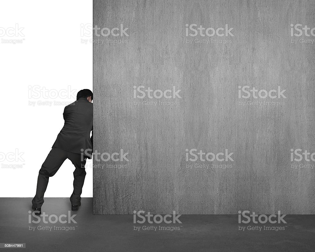 businessman pushing concrete wall away stock photo