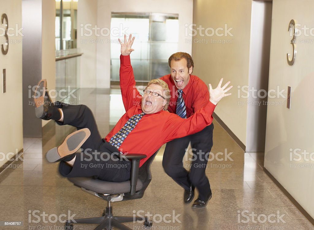 Businessman pushing co-worker in chair in corridor stock photo