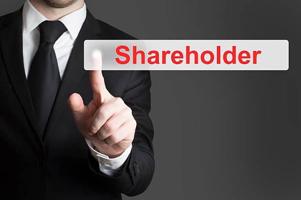 Uomo d'affari spingendo il pulsante piatto per gli azionisti - foto stock