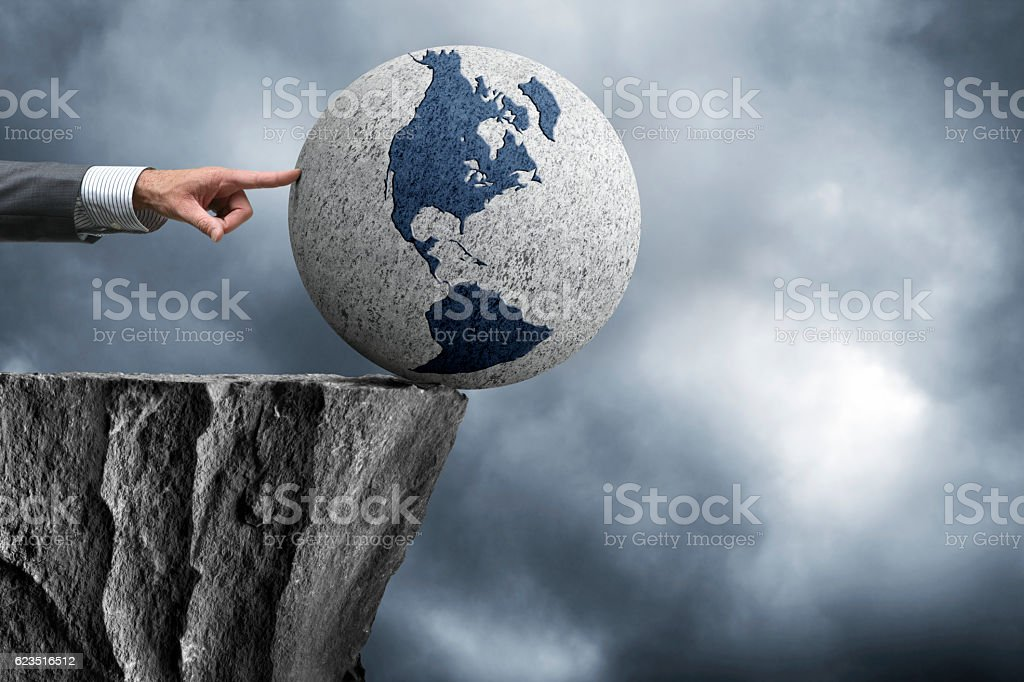 Businessman Pushing Globe Off Edge Of Cliff stock photo