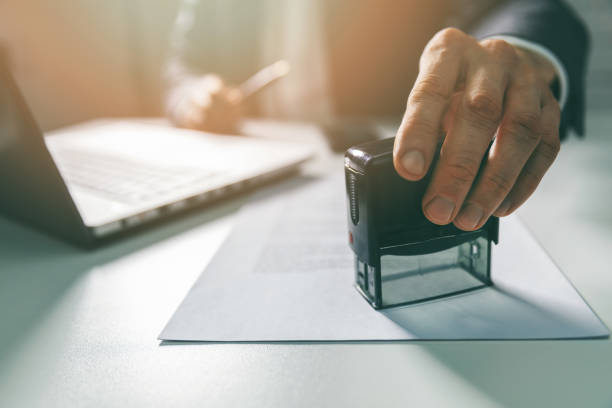 businessman put a stamp on business contract in office stock photo