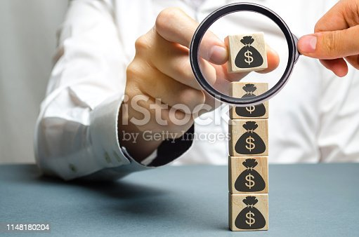 istock Businessman puts a block with a picture of dollars. Increased budget and profits in the team. The capital accumulation and successful business.Increase investment fund. Saving money. Economic boom 1148180204