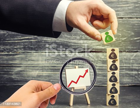 istock Businessman puts a block with a picture of the euro. Increase budget and profits in the team. The capital accumulation, successful business. Investment fund. Saving money. Economic boom. Chart 1133143801