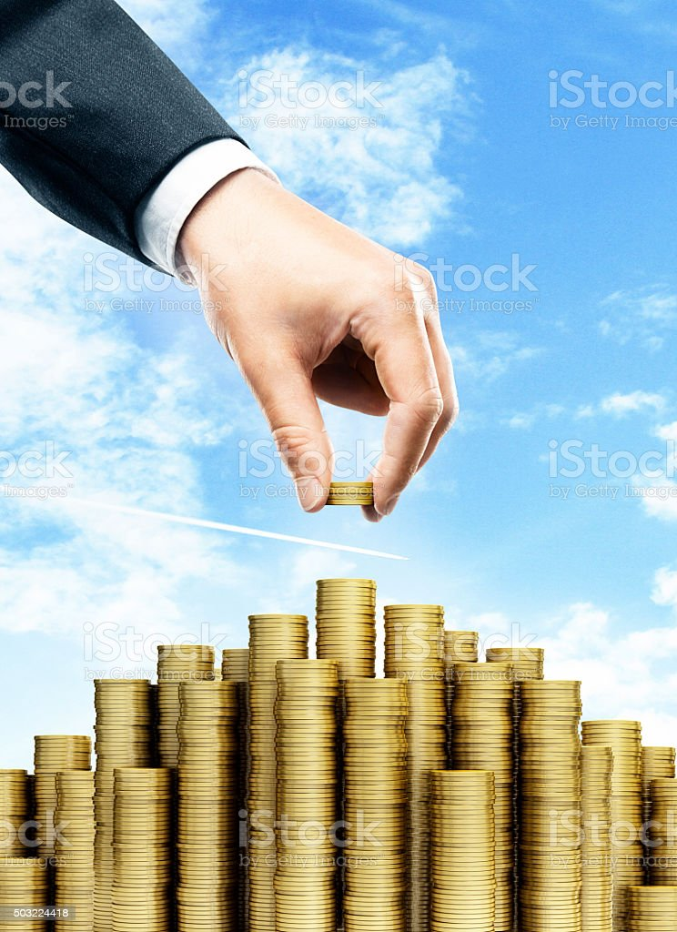 businessman puts a coin stock photo