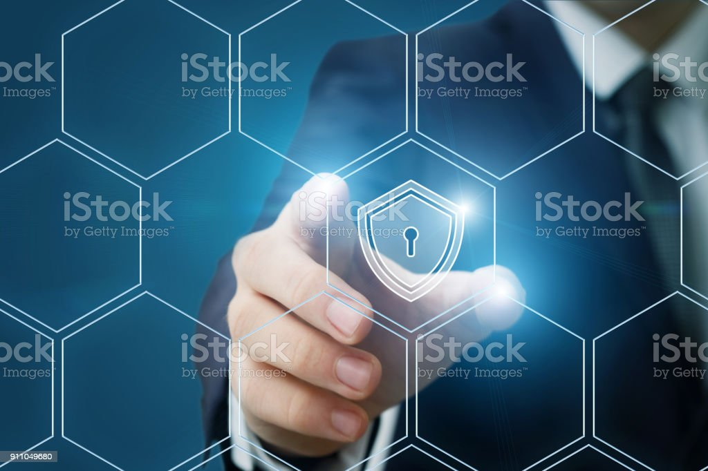 Businessman puts a shield of protection in the system . stock photo