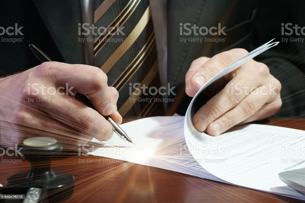 A businessman puts his signature on the contract stock photo