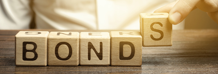 Businessman puts wooden blocks with the word Bonds. A bond is a security that indicates that the investor has provided a loan to the issuer. Equivalent loan. Unsecured and secured bonds.
