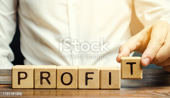 Businessman puts wooden blocks with the word Profit. The financial result of the company for a certain period of time. Income. Return on investment. Performance. Profitable business. ROR, ROI
