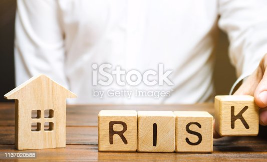 922107104istockphoto Businessman puts wooden blocks with the word Risk and a house. Real estate investment risk. Risky investments. Loss of property for non-payment. Debts. Mortgage tax. Fraudulent schemes. Property 1137020588