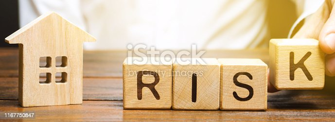 922107104istockphoto Businessman puts wooden blocks with the word Risk and a house. Real estate investment risk. Risky investments. Loss of property for non-payment. Debts. Mortgage tax. Fraudulent schemes. Property 1167750847