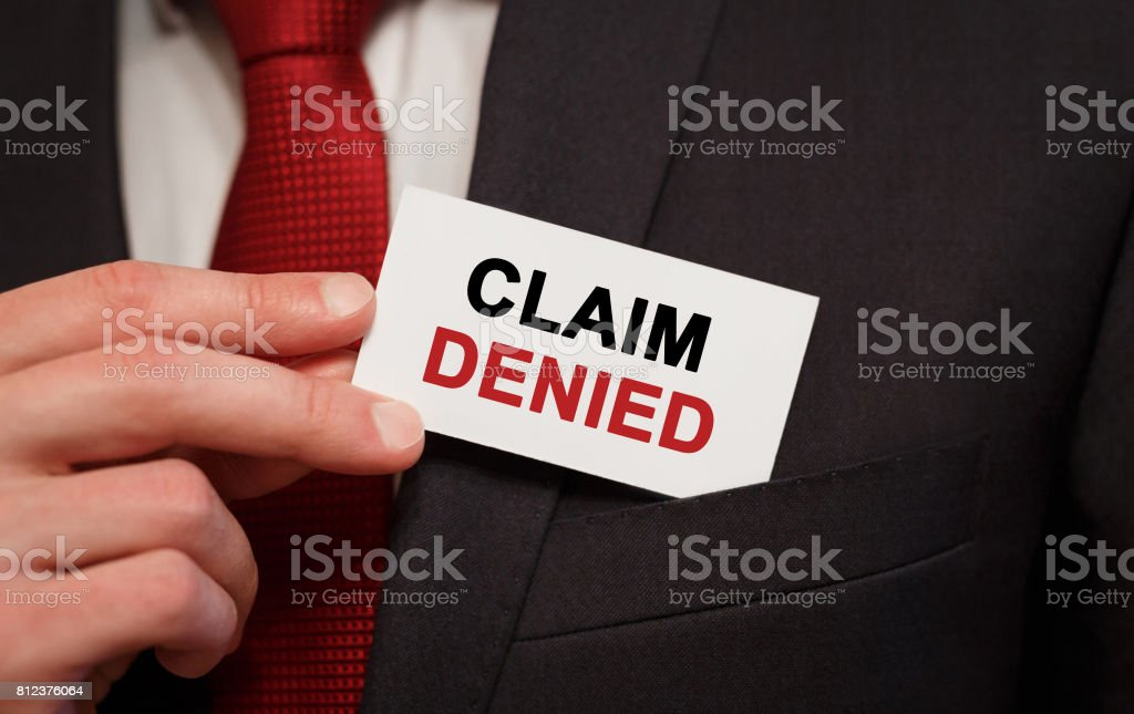 Businessman putting a card with text Claim Denied in the pocket stock photo