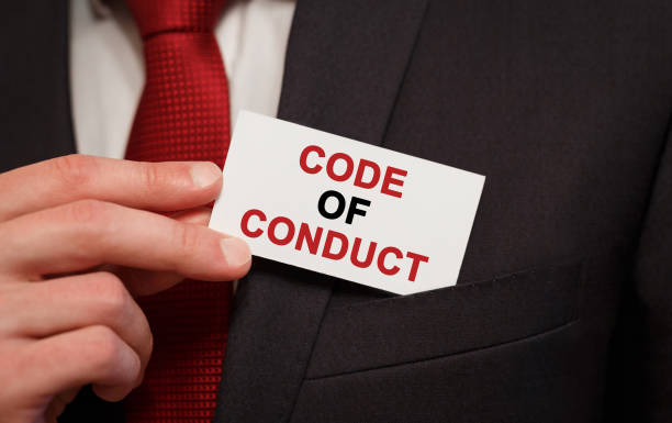 Businessman putting a card with text Code of Conduct in the pocket stock photo